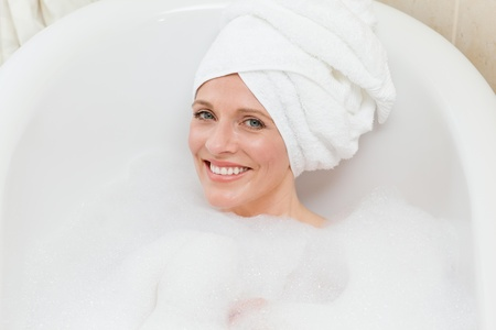 Lovely woman taking a bath with a towel on her head  photo