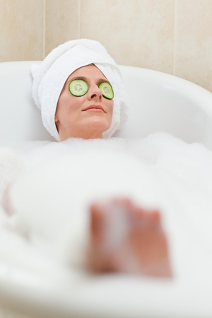 Relaxed woman taking a bath with a towel on her head  photo