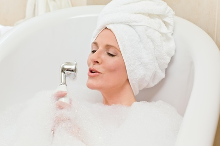 Charming woman taking a bath with a towel on her head  photo