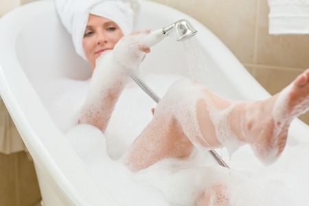 Smiling woman taking a bath with a towel on her head  photo