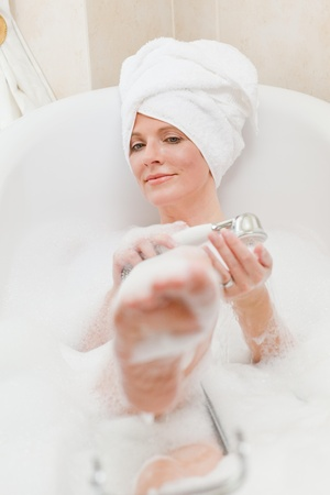 Smiling woman taking a bath with a towel on her head  Stock Photo - 10192985