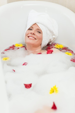 young girl bath: Relaxed woman taking a relaxing bath with a towel on her head  Stock Photo