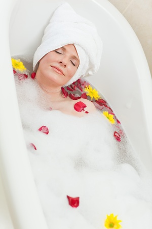 Relaxed woman taking a relaxing bath with a towel on her head  photo