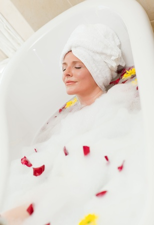 Pretty woman taking a relaxing bath with a towel on her head  photo