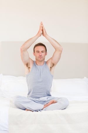 Man practicing yoga on his bed photo