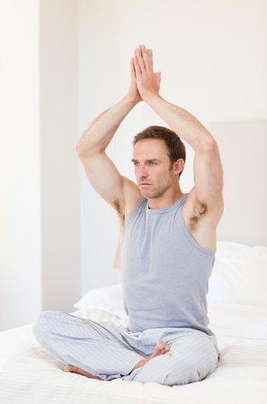 Man practicing yoga on his bed Stock Photo - 10193114