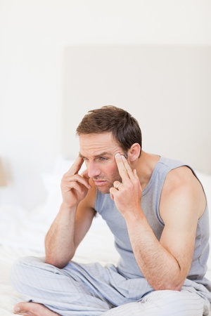 Thoughtful man sitting on his bed photo