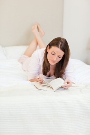 Woman reading a book on her bed photo