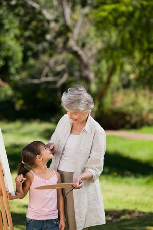 Grandmother and her granddaughter painting in the garden Stock Photo - 10196061