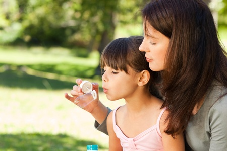 Girl blowing bubbles with her mother in the park photo