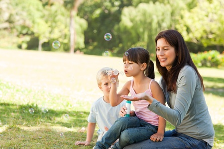 Family blowing bubbles in the park photo