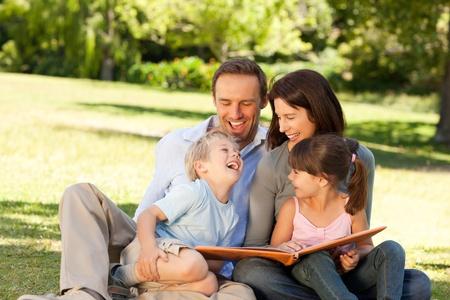 Familia busca a su álbum de fotos en el parque Foto de archivo