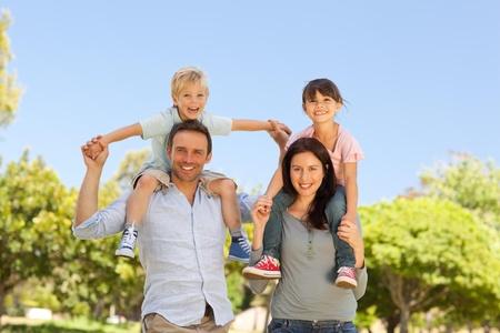 Parents giving  children a piggyback  photo