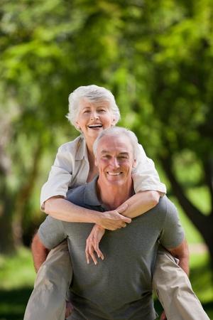 hugging couple: Man giving wife a piggyback Stock Photo