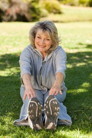 Senior woman doing her streches in the park photo