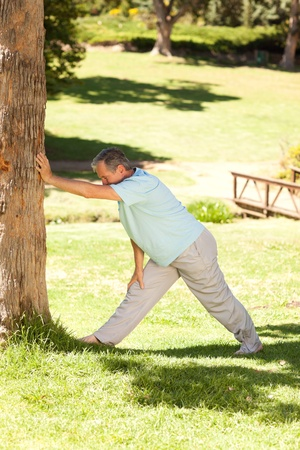 Mature man doing his streches in the park Stock Photo - 10220136