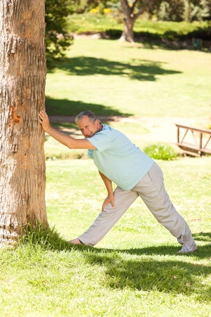 Mature man doing his streches in the park Stock Photo - 10220597