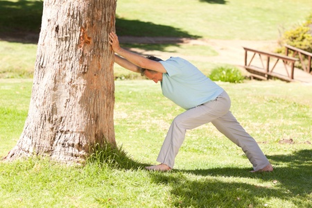 Mature man doing his streches in the park Stock Photo - 10220445