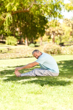 Mature man doing his streches in the park Stock Photo - 10218252