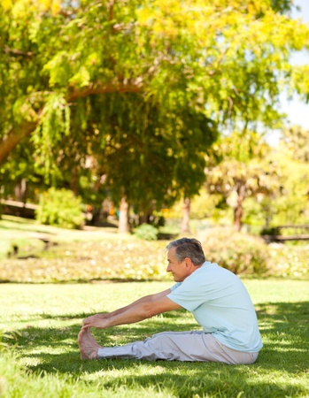 Mature man doing his streches in the park Stock Photo - 10217895