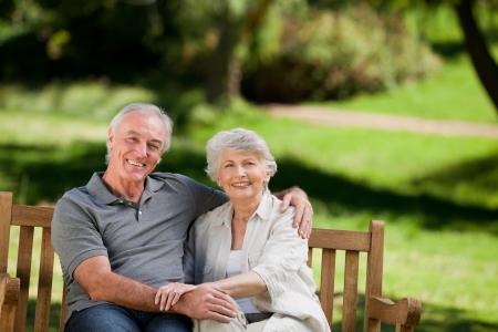 older couples: Senior couple sitting on a bench Stock Photo