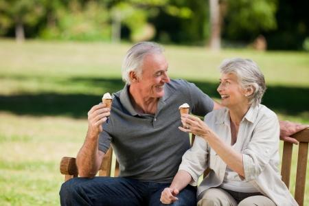 helados: Pareja Senior comer un helado en un banco