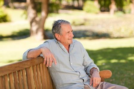 Senior man sitting on a bench photo