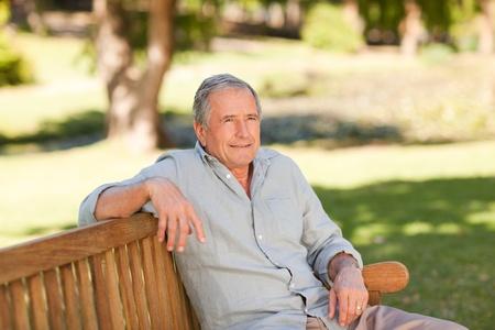 banc de parc: Senior homme assis sur un banc Banque d'images