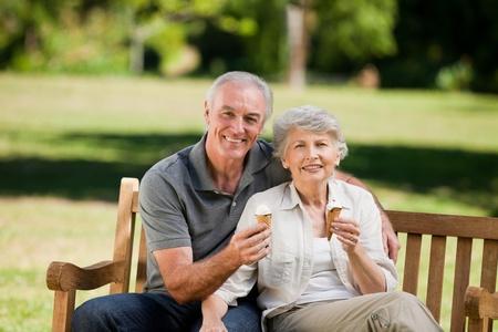 pareja comiendo: Pareja Senior comer un helado en un banco