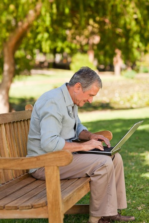 one mid adult man: Elderly man working on his laptop in the park Stock Photo