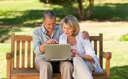 one mid adult male: Senior couple working on their laptop