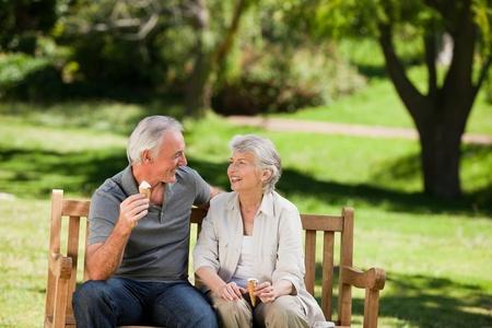 comiendo helado: Pareja Senior comer un helado en un banco