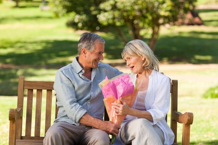 Mature man offering flowers to his wife photo