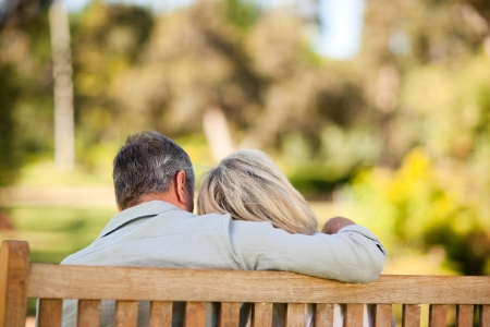 woman middle age: Elderly couple sitting on the bench with their back to the camera