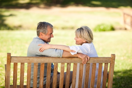 middle age man: Happy retired couple sitting on the bench Stock Photo