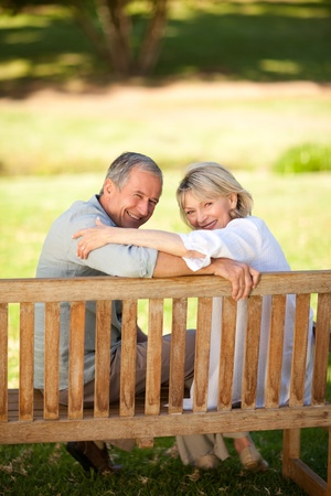 one mid adult male: Happy retired couple sitting on the bench Stock Photo