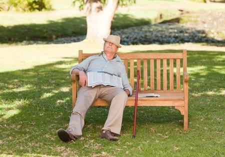 one senior adult man: Senior man sleeping on the bench