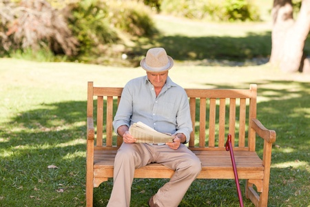 one senior: Retired man reading his newspaper on the bench Stock Photo