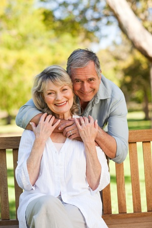 middle age man: Elderly man hugging his wife who is on the bench