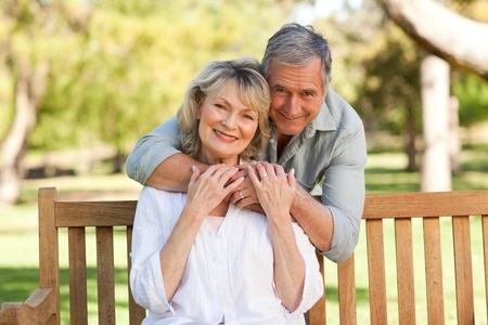 Elderly man hugging his wife who is on the bench photo