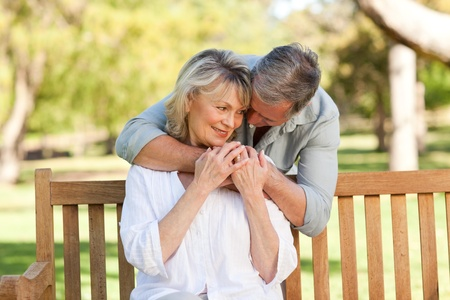 middle age couple: Elderly man hugging his wife who is on the bench