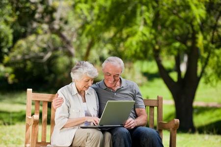 pareja abrazada: Pareja de ancianos mirando su port�til Foto de archivo
