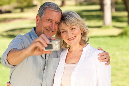 Elderly couple taking a photo of themselves in the park Stock Photo - 10217836