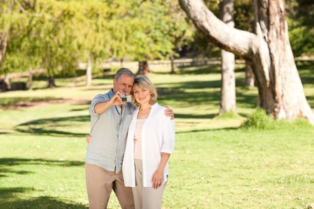 Elderly couple taking a photo of themselves in the park photo