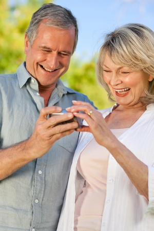Mature couple looking at their camera photo