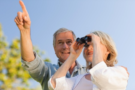 Couple looking at the sky with their binoculars photo