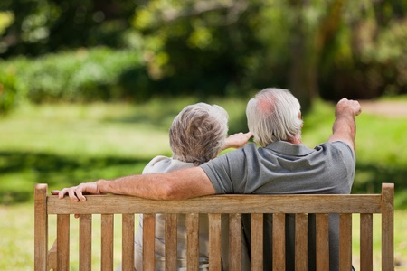 love seat: Couple sitting on the bench  with their back to the camera Stock Photo