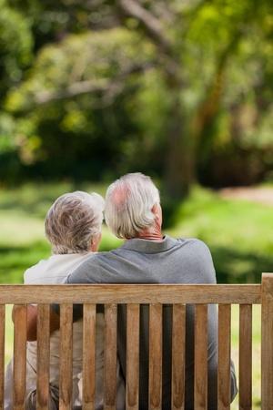 jubilados: Pareja sentada en el banquillo con su espalda a la c�mara Foto de archivo