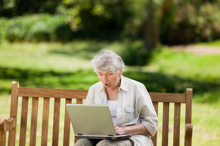 Mature woman working on her laptop on the bench photo