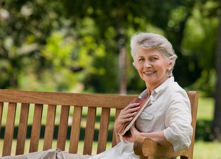 Retired woman reading a book on the  bench Stock Photo - 10215497